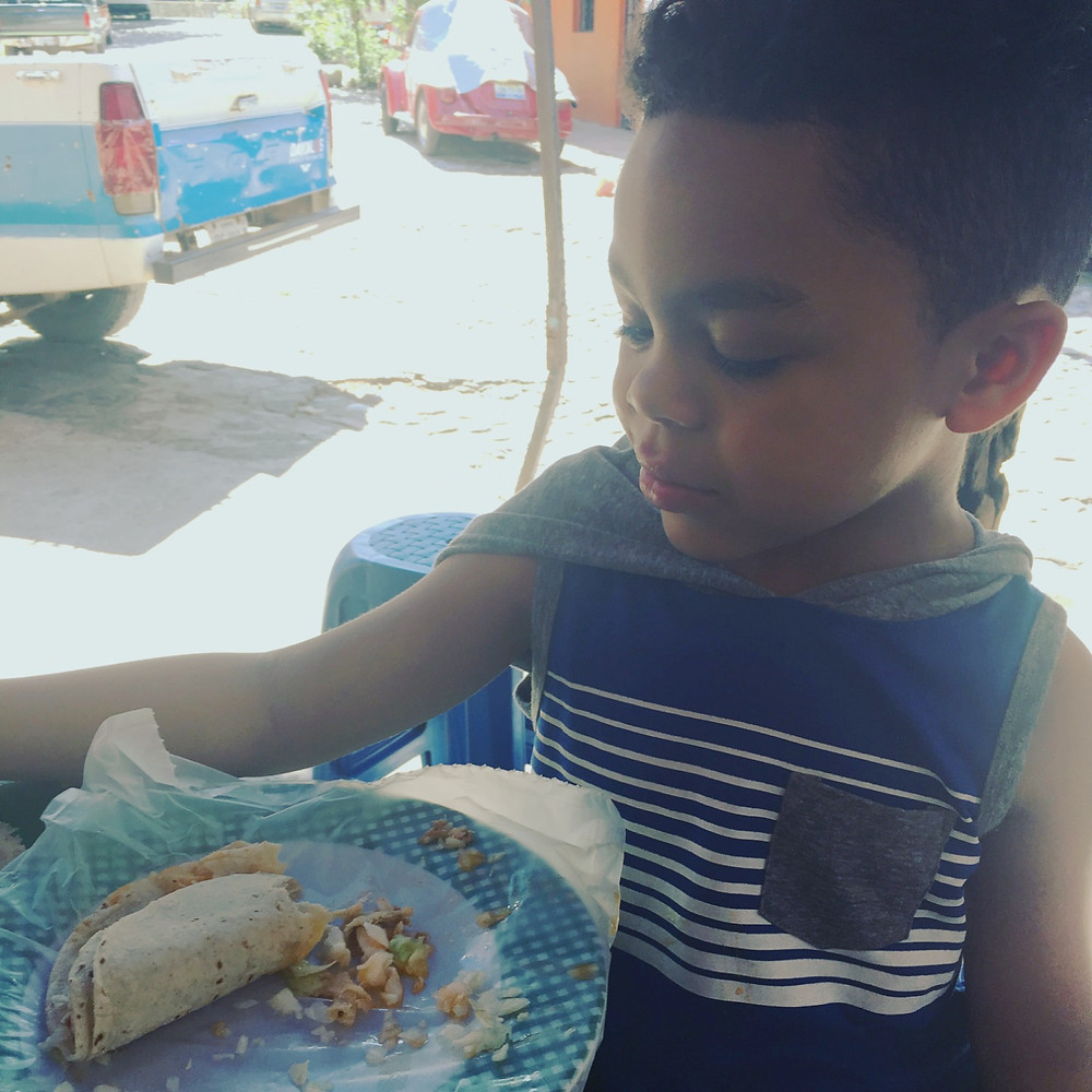 Boy attempts to eat a street taco in Mexico.