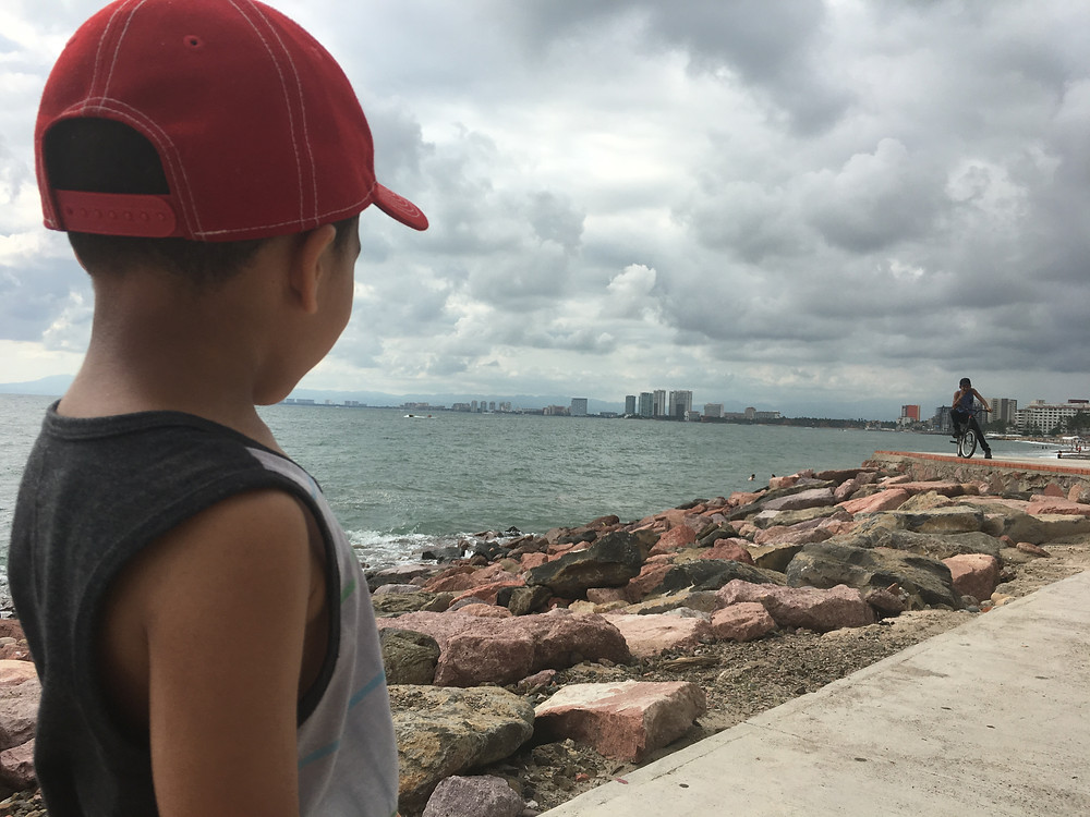 Boy on beach makes eye contact with man in the distance.