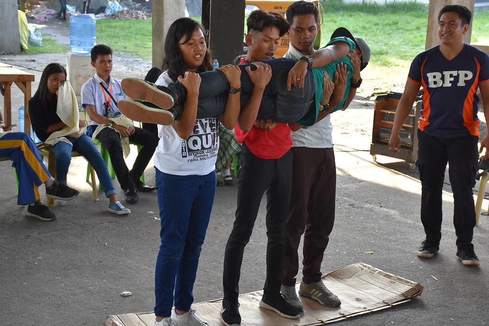 Youth participants actively cooperate by posing as victim and first aid responders during their workshops on the application of their learned skills in relation to first aid administration.