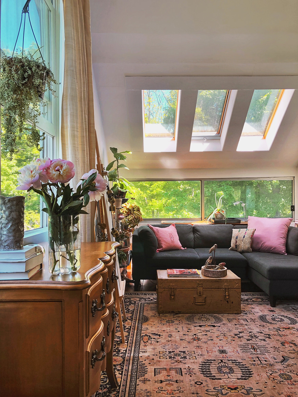 Green trees outside windows, pink rug, gold furniture