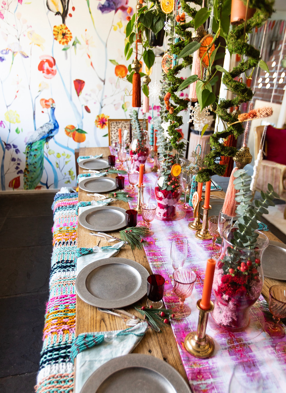 Hanging moss over holiday table set up with pink runner and floral wallpaper