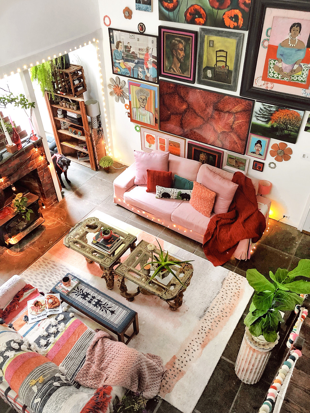 Arial view of living area with pink, red, yellow decor. Maximalist cozy space