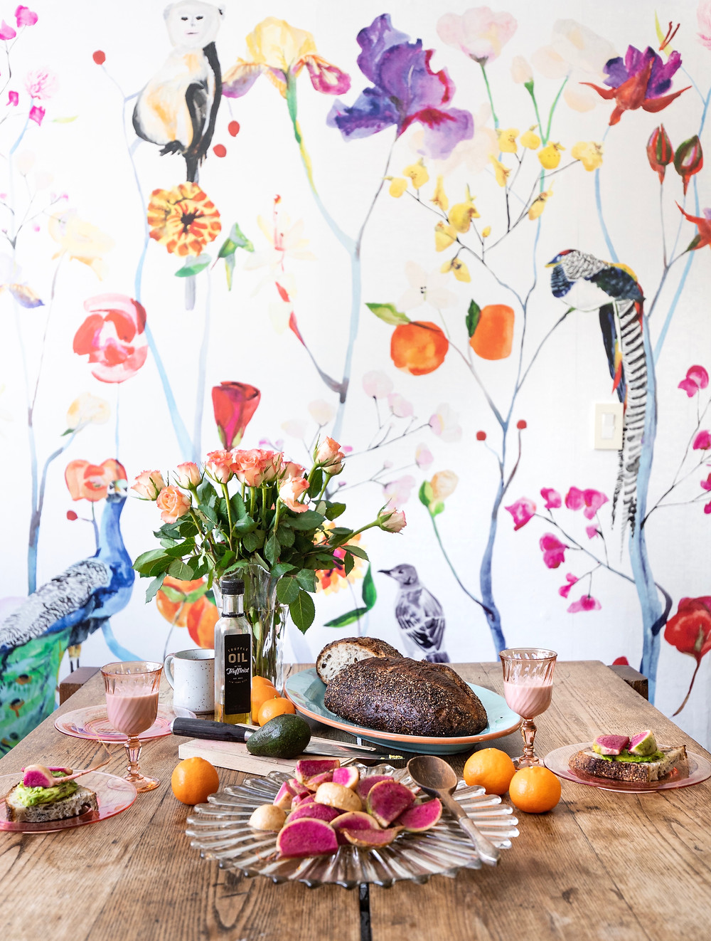 Brunch table with avocado, radish sandwich. Floral wallpaper and flower arrangement