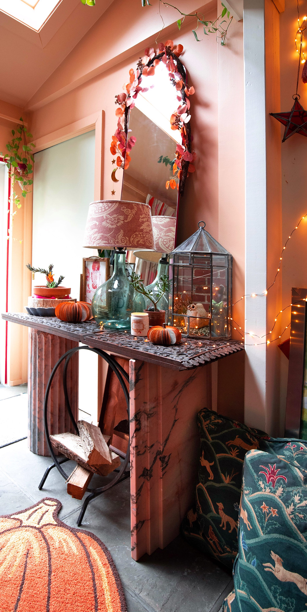 Front hall fall table decor with pink/orange eucalyptus garland, gold moon and star garland, paper book handmade pumpkins, engraved wood table top, terrarium with owls. Pink marble base, arched mirror.