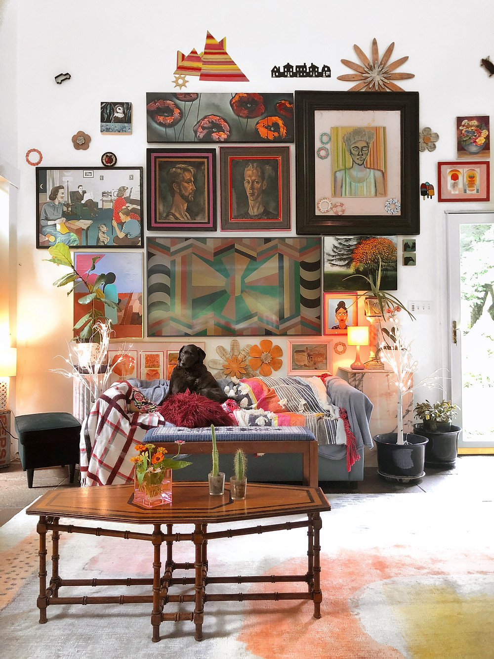Colorful gallery wall in living room with pink, red and oranges.