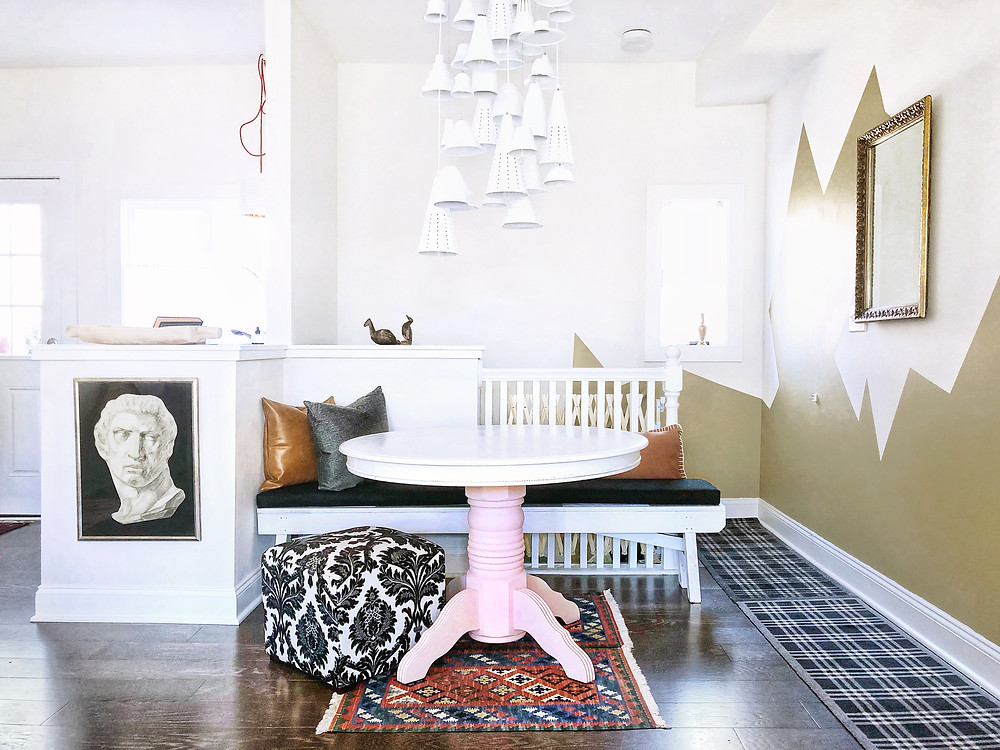 Stylish Airbnb with mountain mural and pink table base. Modern pendant light