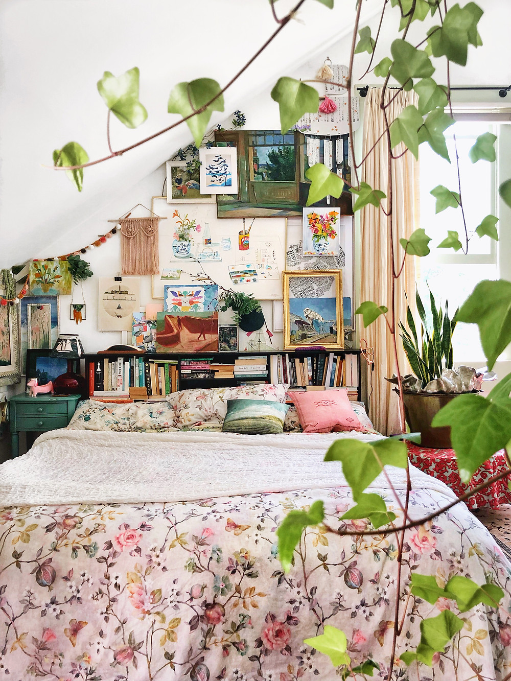 Layered gallery wall over bed with plants and floral bedding