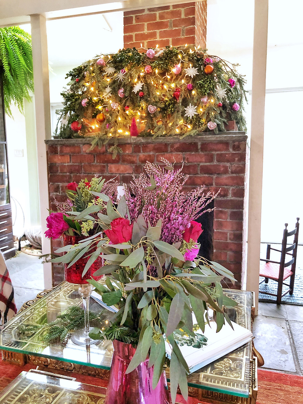 fireplace mantle with thick garland and floral arrangement