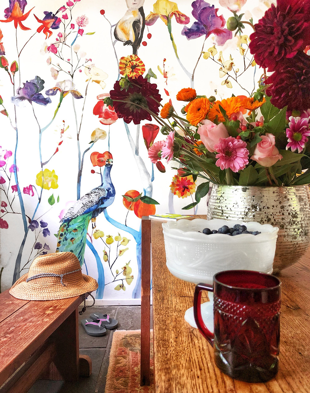 Floral wallpaper with vintage glass and bowl. Organic bouquet in the background with a summer hat and flip flops