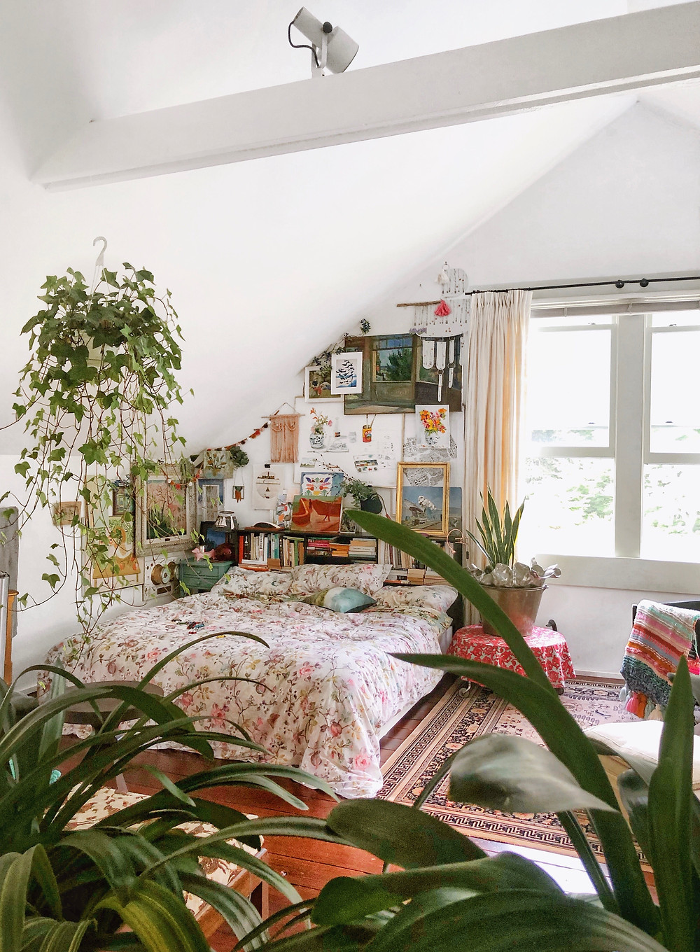 Loft bedroom with plants and gallery wall
