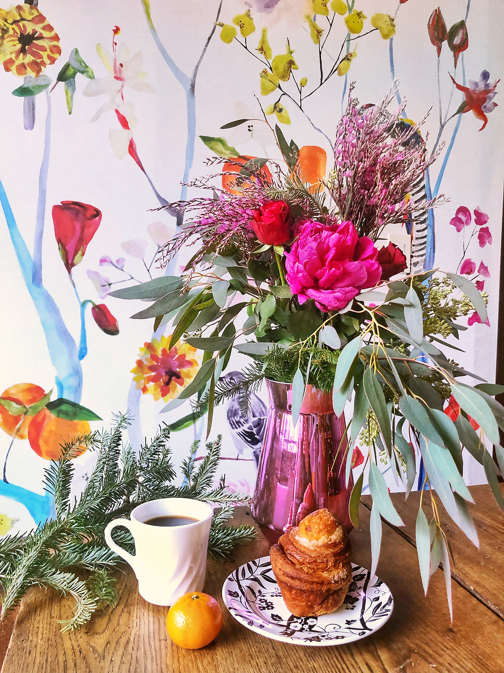 Flowers over breakfast. Coffee, danish and orange. Floral wallpaper with wood table