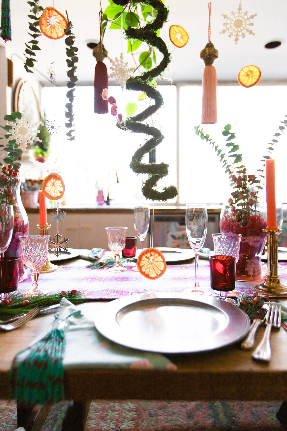 Cheerful holiday table setting with moss, dried citrus, snowflakes, tassels, vintage tableware