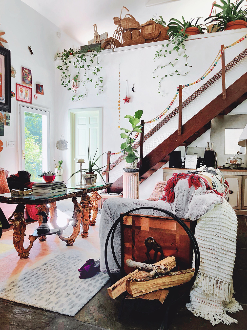 Plants dangling from ledge in living room, log pile ready, mermaid coffee table