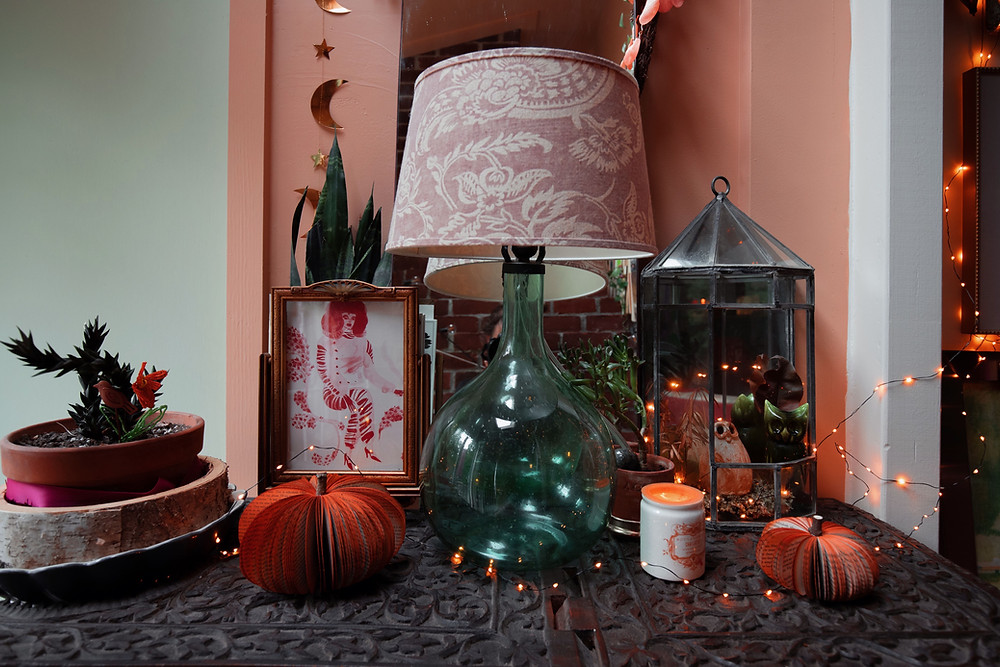 Front hall fall table decor with pink/orange eucalyptus garland, gold moon and star garland, paper book handmade pumpkins, engraved wood table top, terrarium with owls.
