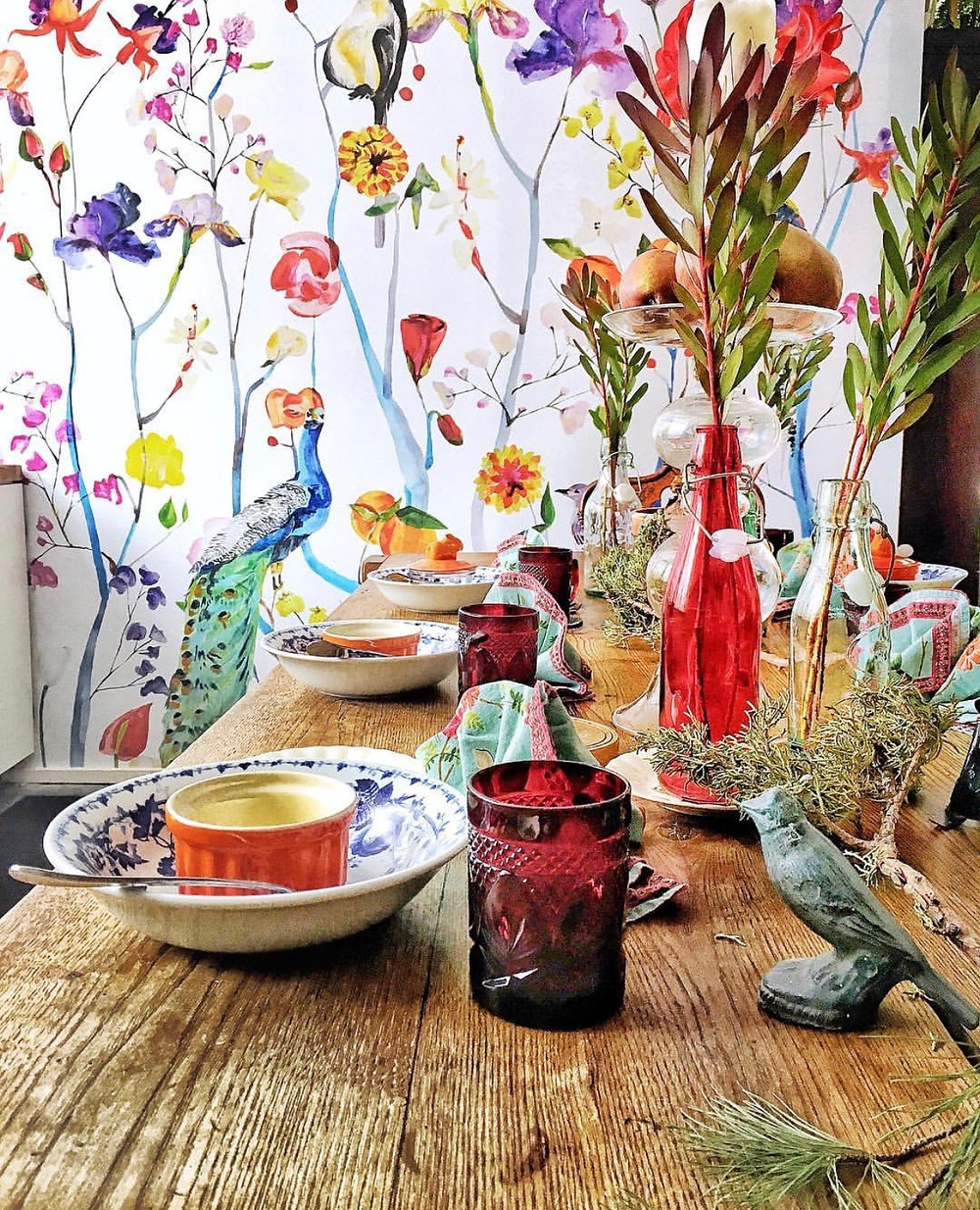 floral wallpaper, red vintage cups, table setting with a whimsical style