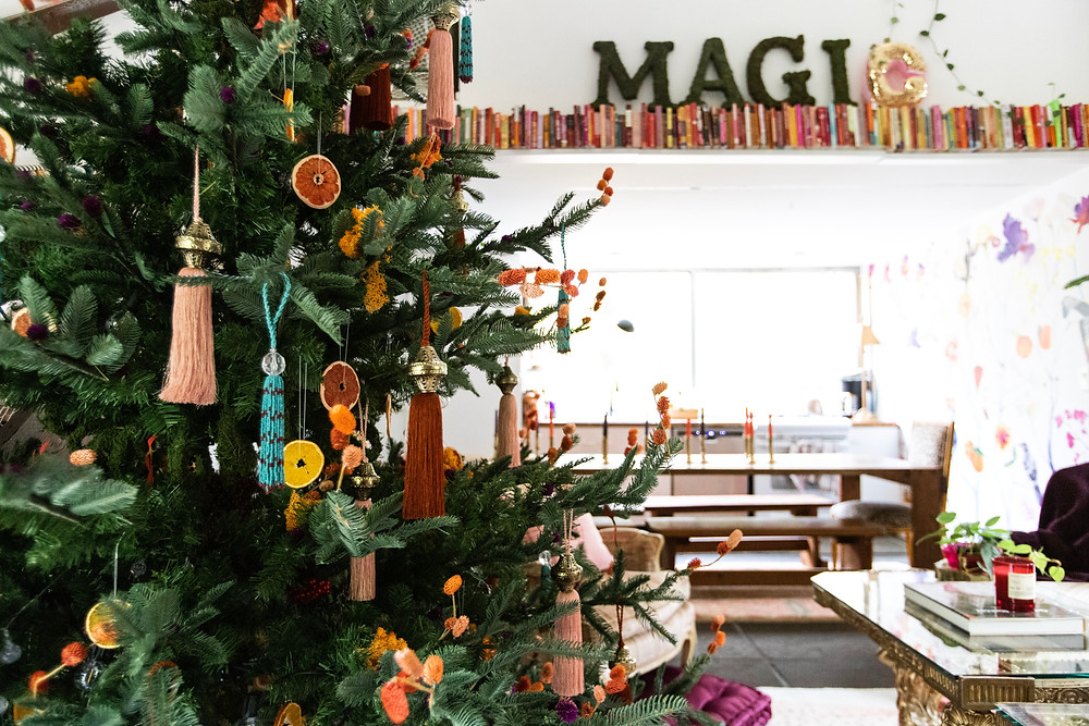 Christmas tree with tassels, pink books, magic, and citrus slices