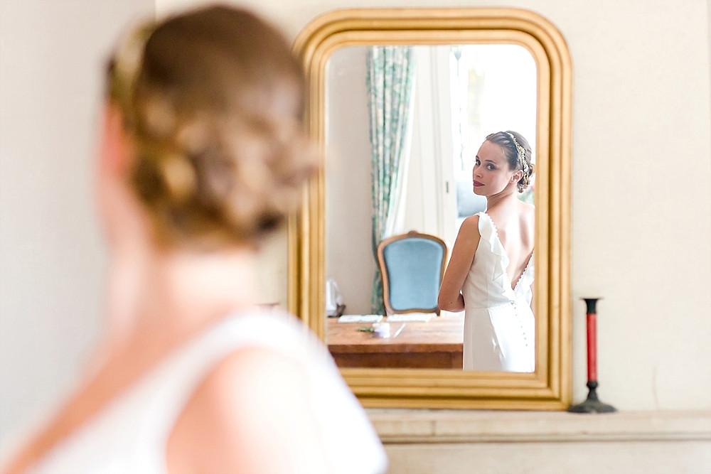 La mariee enfin prete se regarde dans un miroir