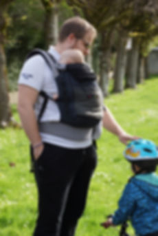 Papa porte son bébé en porte-bébé écharpe de portage