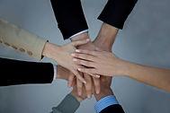 チーム一丸。全員で片手の手のひらを合わせて意識を高めている。コミュニケーション作り。
