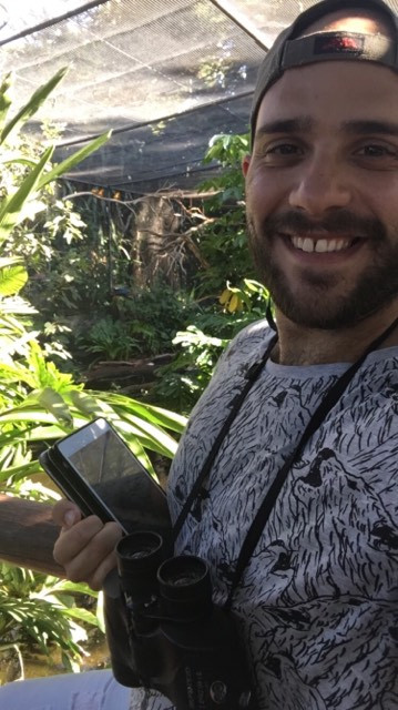 "Ricardo looking very happy while practising his data collection at Perth Zoo's ""Tropical Birds"" enclosure. Three sun conures (Aratinga solstitialis) can be seen at the back."