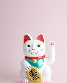 a Maneki-neko plastic cat, Symbolizing l