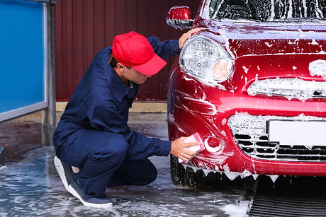 Man cleaning automobile with sponge at c