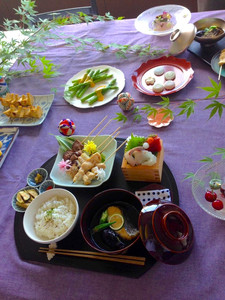 Japanese full course meal also using various dishes and decoration - rice, soup, yakitori , sashimi, egg rolls, vegetables and cherry