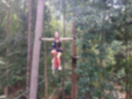 Riding a bike on a tight rop in te tree tops at Skytrex adventures in Melacca