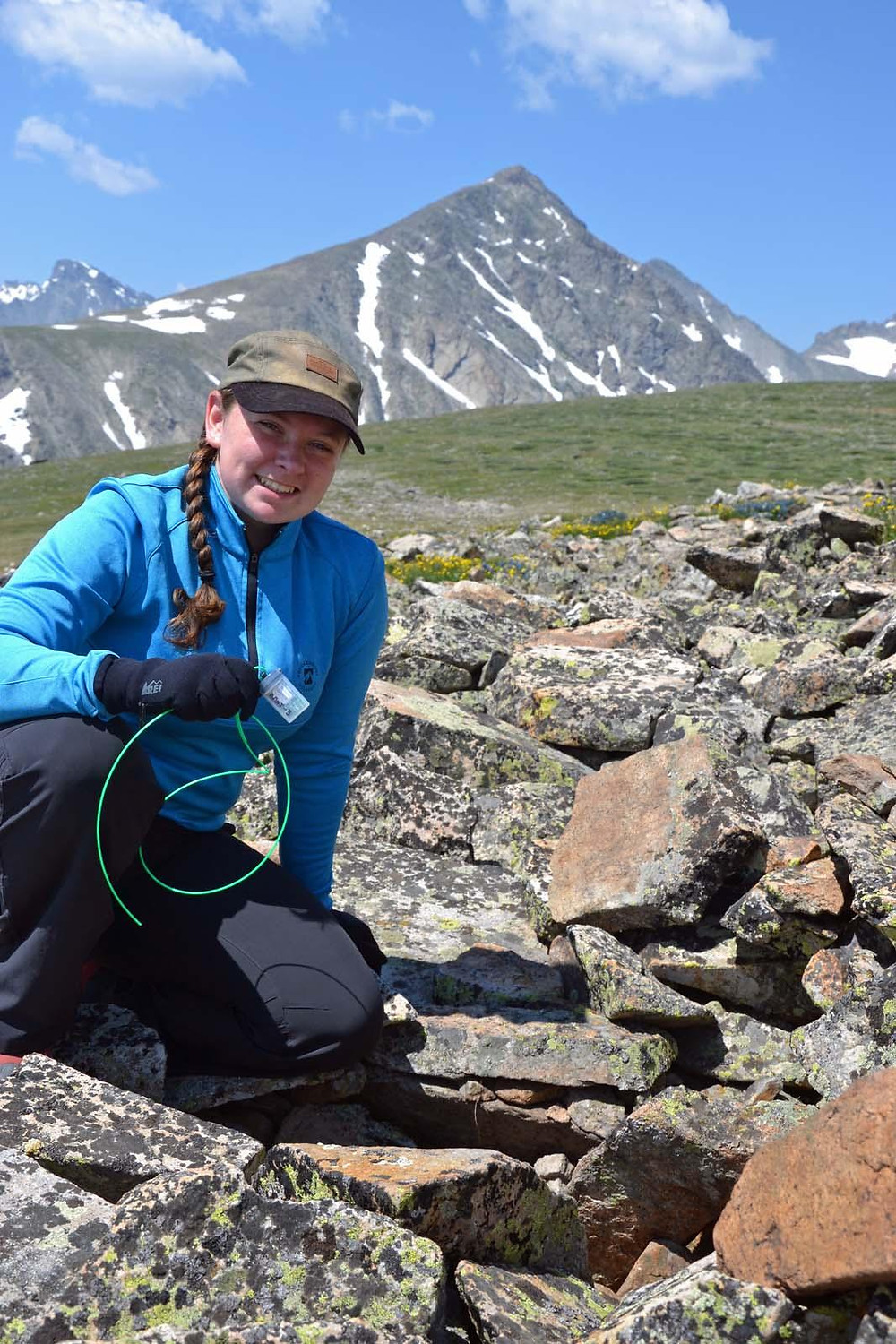 Emily placing a temperature sensor in a place that used to be occupied by pikas