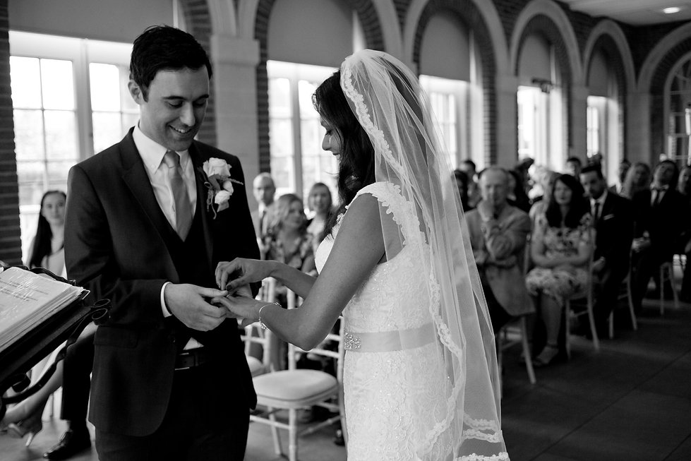 The exchanging of rings. Great Fosters Wedding, The Orangery & Conservatory at Great