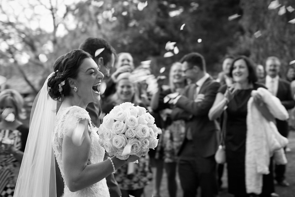 Wedding ceremony at Emu Bottom Homestead. Just married! Bride looking very excited with the confetti being thrown around.