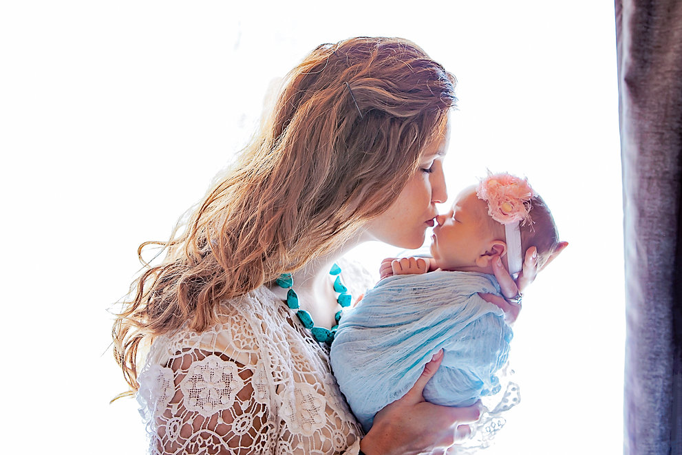 mother kissing newborn photography
