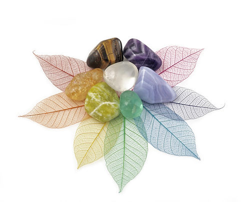 Healing Chakra Crystals on Leaves  -  Chakra colored tumbled crystals placed on an arrangement of ra