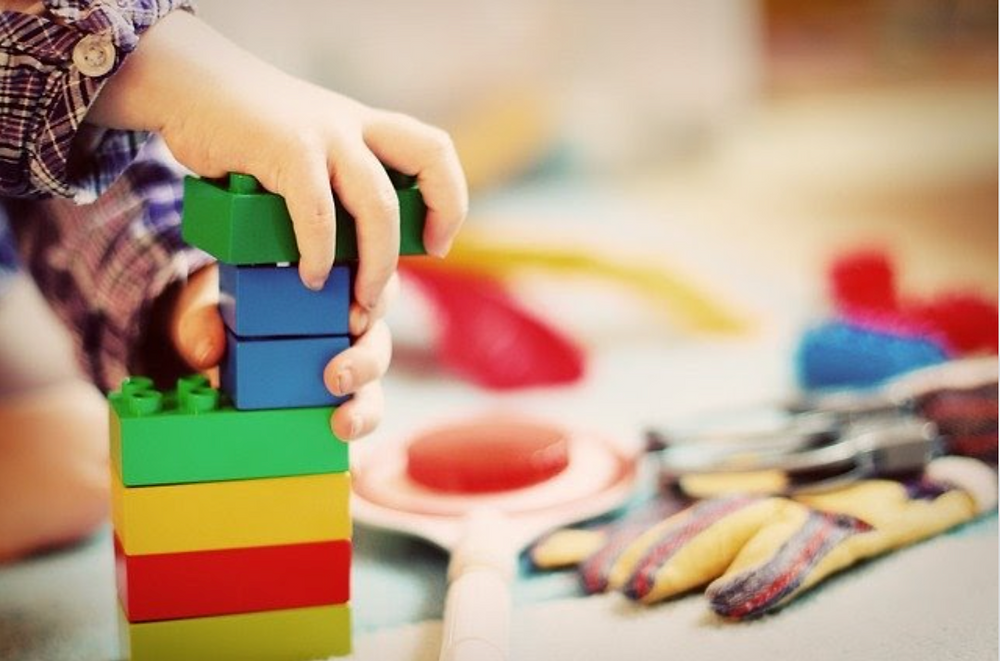 child's hands playing with blocks