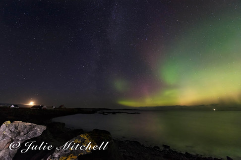 Northern lights and the milky way reflected in the sea.