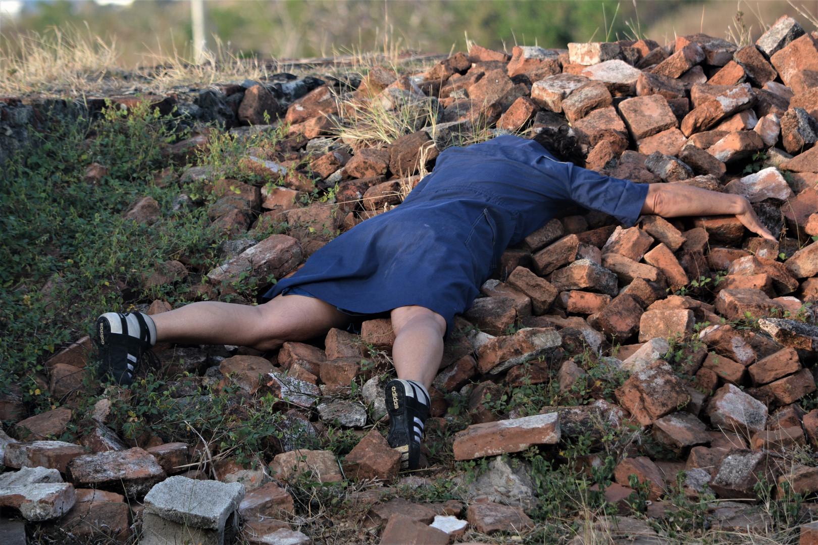 Mujer desplomada en ladrillos