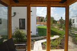 Výhled z venkovní sauny do privátního prostoru zahrady u frekventované komunikace Praha