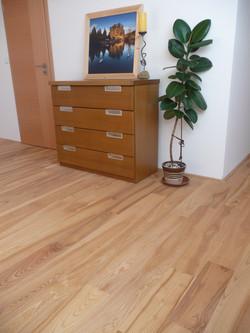 Dřevěná podlaha a dýhovaná komoda