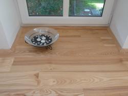 Skleněná miska a jasanová podlaha