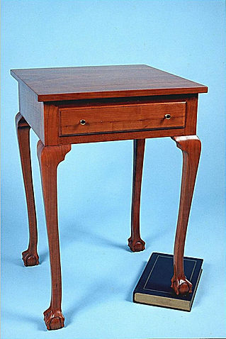 cherry table with carved book under leg