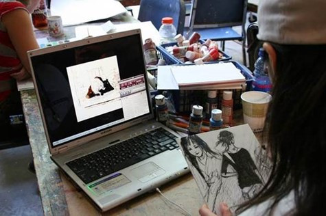 Artist at work on computer and paper