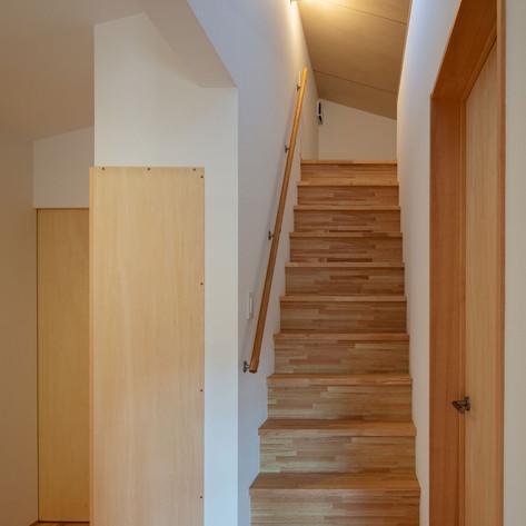 この階段を上がると上部はロフトスペース。ロフトに固定の階段(固定でないと、はしごになってしまう)をつけて良いかどうかは、建設する地域の行政機関の判断によります。