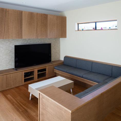 L字型の造り付けのソファーに、エアコンを組み込んだ大型の吊り戸、そしてTVボード。全て統一感のある造り付け家具です。左手の布状のものはハンモック。