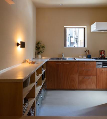 コンクリート土間と珪藻土の壁にテラゾーカウンターとラワンベニア家具のL字型キッチン