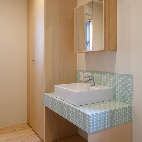 天井いっぱいの収納は容量があり、何かと散らかる洗面脱衣もスッキリ。モザイクタイルでがっちり洗面カウントを作り、暖かい感じとした。