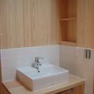 木のカウンターにベッセル式洗面。立ち上がりの壁を一部タイル貼りとしました。汚れ防止とデザイン的な意味も込めた提案です。