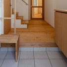 玄関には収納量を検討した下駄箱と高齢者用のベンチと縦手すりを設置している