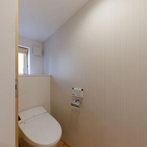 奥に行くほど天井が低くなる勾配天井のトイレ。便座の上の寸法を調整しながら合理的な間取りを検討した結果である。