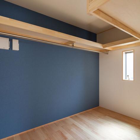 コの字型の棚と洋服掛けのある寝室脇のウォークインクローゼット。
