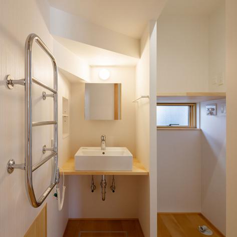 1階階段下に設けられた洗面スペース。階段の下も無駄にしません。手前足元収納も階段下の空きスペースを利用しています。左手壁面にあるのはタイルウォーマー。便利です。